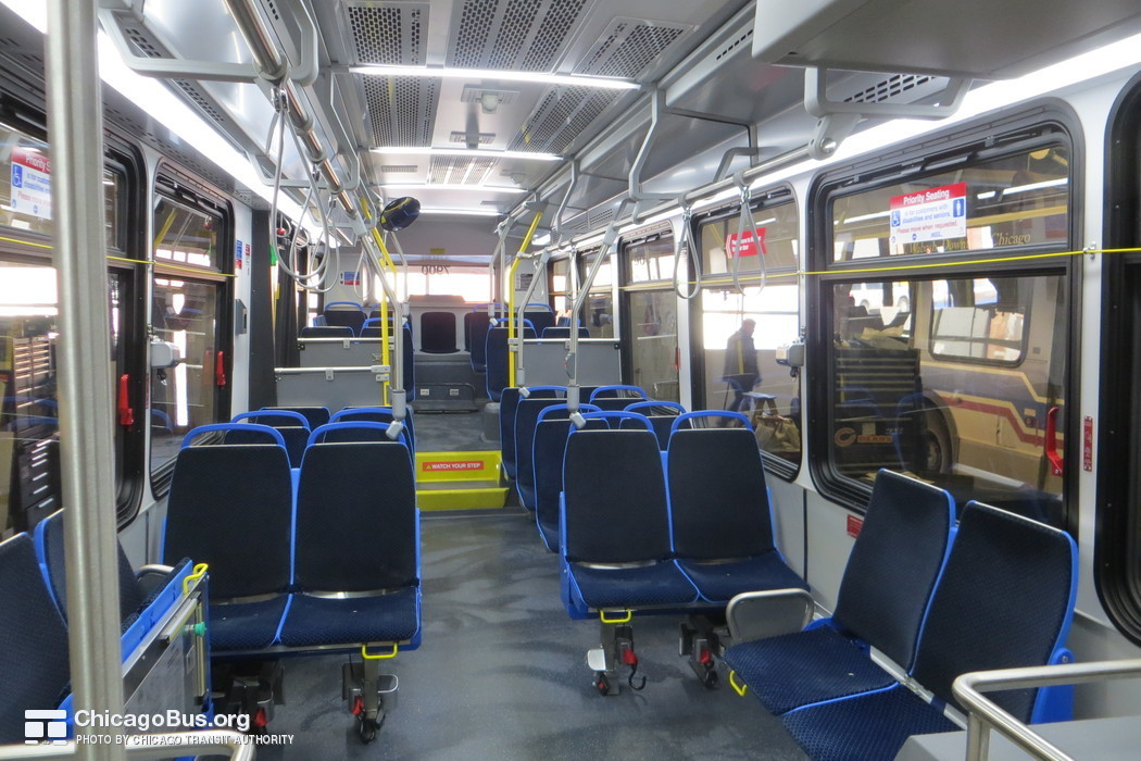 "The interior of bus #7900 at CTA's South Shops Maintenance Facility on February  6, 2014. The interior of the 7900-series Novas features several departures from past models. The buses feature new lightweight ""Gemini"" model seats from Chicago-based Freedman Seating Company. A new slate gray seamless floor design replaces the deep blue grooved flooring that CTA has traditionally used in its bus fleet. Rows of lights now span across the aisle in addition to the traditional rows of lights along the sides of the bus. An improved bulkhead design along the driver's side of the bus provides for increased vertical clearance."